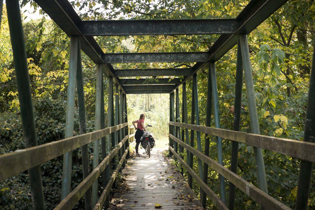 noia amb bicicleta esperant al final d'un pont