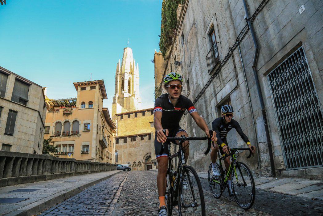 dos ciclistes de carretera a la pujada de sant Feliu de Girona
