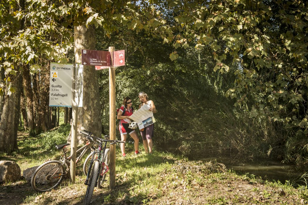 Dues ciclistes consulten un mapa a peu de camí